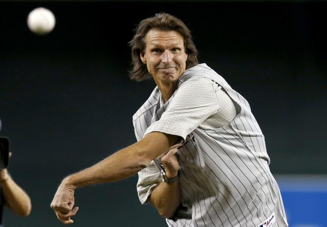 Former Arizona Diamondbacks pitcher Randy Johnson throws out the first pitch during ceremonies commemorating the 10th anniversary of Johnson's perfect game prior to a baseball game between the Diamondbacks and the Los Angeles Dodgers on Sunday, May 18, 2014, in Phoenix. (AP Photo/Ross D. Franklin)