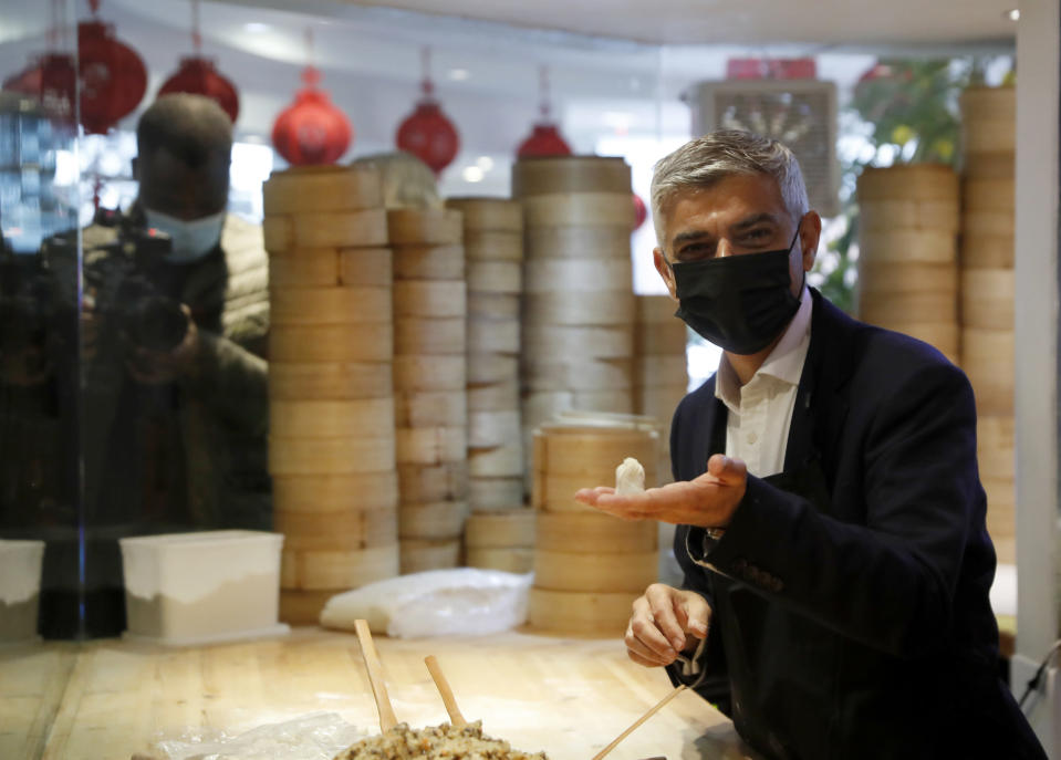 FILE - In this file photo dated Monday, May 17, 2021, Mayor of London Sadiq Khan, holds a dumpling he prepared, during a visit to Dumplings Legend in China Town central London. Khan on Thursday July 22, 2021, sent a message of support to Hong Kong people fleeing China's crackdown on democracy to seek a new life in the U.K., saying his office will spend 900,000 pounds (dollars 1.2 million US) to help new arrivals with housing, education and finding jobs. (AP Photo/Alastair Grant, FILE)