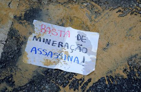 """A paper that reads; """"Enough of murderous mining!""""  is seen on a street during a protest against Brazilian mining company Vale SA in Belo Horizonte, Brazil January 31, 2019. REUTERS/Washington Alves"""
