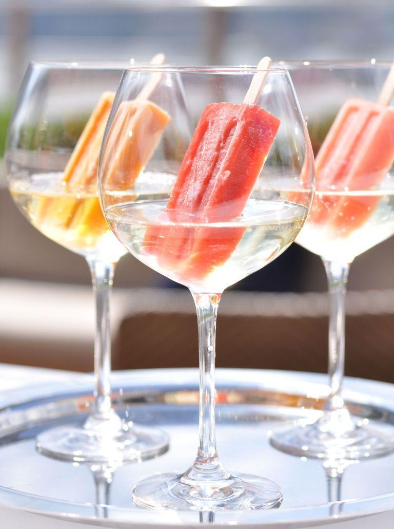 """<p>For a summery treat, drop a colorful ice pop into your glass of white wine. You'll want to try every flavor in the box before summer ends. </p><p><em><a href=""""https://www.goodhousekeeping.com/food-recipes/dessert/a33589/popsicle-in-champagne/"""" rel=""""nofollow noopener"""" target=""""_blank"""" data-ylk=""""slk:Get the recipe for Popsicle Cocktails »"""" class=""""link rapid-noclick-resp"""">Get the recipe for Popsicle Cocktails »</a></em> </p>"""