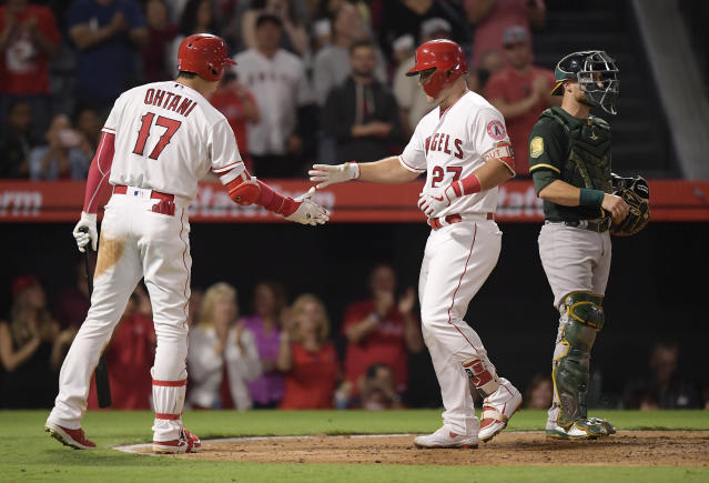Los Angeles Angels' Mike Trout, center, is congratulated by Shohei Ohtani, left, of Japan, after hitting a two-run home run, while Oakland Athletics catcher Jonathan Lucroy stands at the plate during the third inning of a baseball game Friday, Sept. 28, 2018, in Anaheim, Calif. (AP Photo/Mark J. Terrill)