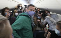 FILE - In this Jan. 17, 2021, file photo, Alexei Navalny is surrounded by journalists inside the plane prior to his flight to Moscow in the Airport Berlin Brandenburg (BER) in Schoenefeld, near Berlin, Germany. Allies of Navalny are calling for new protests next weekend to demand his release, following a wave of demonstrations across the country Saturday, Jan. 23, that brought out tens of thousands in a defiant challenge to President Vladimir Putin. (AP Photo/Mstyslav Chernov, File)