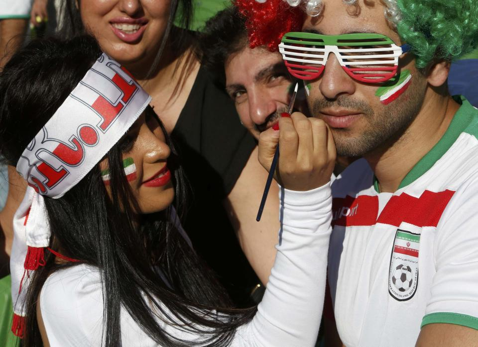 An Iran supporter applies face paint to another fan before the Asian Cup Group C soccer match betweeen Iran and Bahrain at the Rectangular stadium in Melbourne January 11, 2015. REUTERS/Brandon Malone (AUSTRALIA - Tags: SOCCER SPORT)