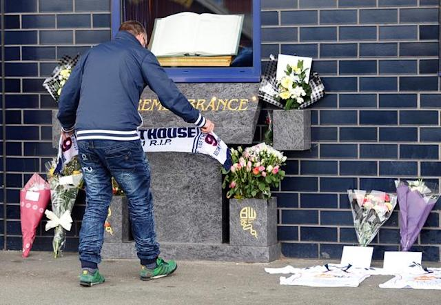 A man lays a scarf alongside football shirts and flowers left outside the Reebok Stadium in Bolton, north-west England on March 18, 2012 the morning after Bolton Wanderers' English midfielder Fabrice Muamba collapsed during their FA cup football match against Tottenham Hotspur in London. The 23-year-old Kinshasa-born player was rushed to hospital after harrowing scenes towards the end of the first half at White Hart Lane on Saturday, when the midfielder slumped to the turf with no player near him. TOPSHOTS AFP PHOTO / PAUL ELLIS