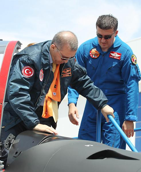 """Turkish Prime Minister Recep Tayyip Erdogan, left, gets into cockpit of a Hurkus (Freebird), Turkey's first locally produced military training plane, a two-seat turboprop plane, unveiled during a ceremony outside Ankara, Turkey, Wednesday, June 27, 2012. Erdogan kept up his pressure on Syria on Wednesday, saying """"we would never hesitate to respond with all our power to hostile acts, attacks and threats against us."""" AP Photo)"""