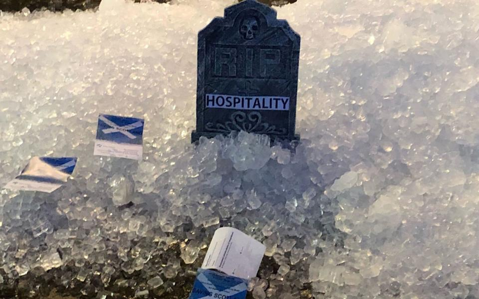 "Mini gravestone reading ""RIP hospitality"" alongside Scotland flags  - PA"