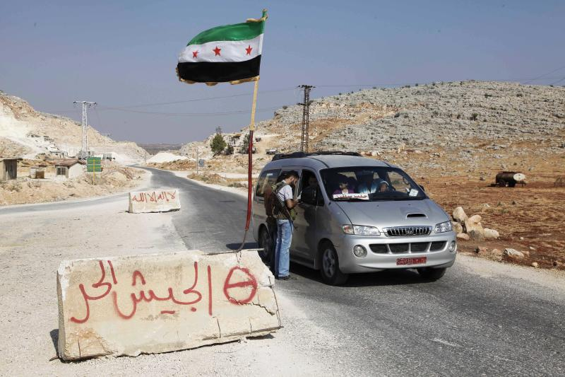 "In this Tuesday, July 31, 2012 photo, a Free Syrian Army soldier stands at a check point in Maarat Misrin in Idlib province, Syria. Arabic on the barriers read, ""no God but Allah,"" background, and ""Free Syrian Army,"" foreground. (AP Photo)"