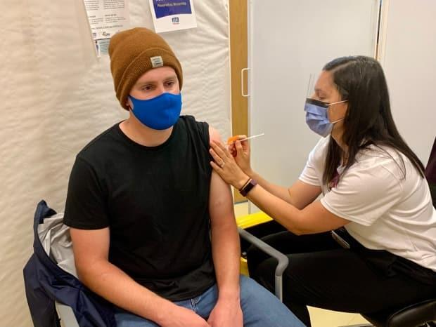 Steven Marenick of Halifax gets a COVID-19 vaccine at the IWK clinic. The clinic is being extended after hundreds of people showed up on Friday for last-minute shots.   (Paul Palmeter/CBC - image credit)