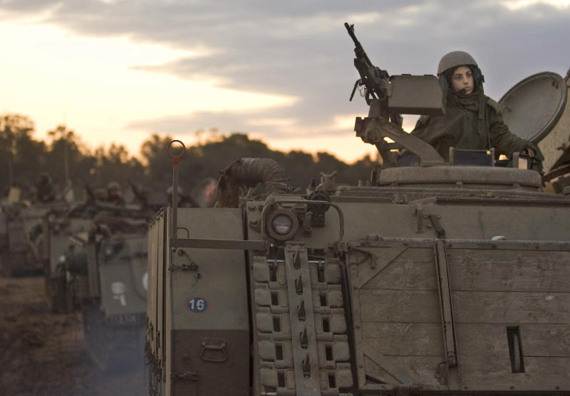 FILE - In this Monday, Jan. 12, 2009 file photo a female Israeli soldier sits atop an armored vehicle as it drives towards Israel's border with the Gaza Strip on a combat mission. From France's Joan of Arc, to female resistance fighters of World War II and the black-clad women warriors of the Viet Cong, popular history is filled with stories of women fighting alongside men in epic struggles. The image of the gun-toting Israeli woman warrior is widely seen as the prototype of a gender-blind military. Reality is different. Israeli women are subject to the draft — serving two years while men serve three. But women were barred from direct combat until 2000, when the first and so far only mixed gender infantry battalion was organized. (AP Photo/Sebastian Scheiner, File)