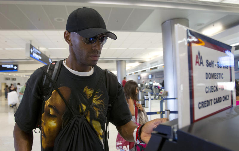 In this Friday, June 29, 2012 photo, Walter Diaz, of Miami, checks-in at Miami International Airport in Miami. Diaz, who is traveling to New Jersey on business, will not be traveling on the Fourth of July because the holiday falls on a Wednesday. (AP Photo/Alan Diaz)