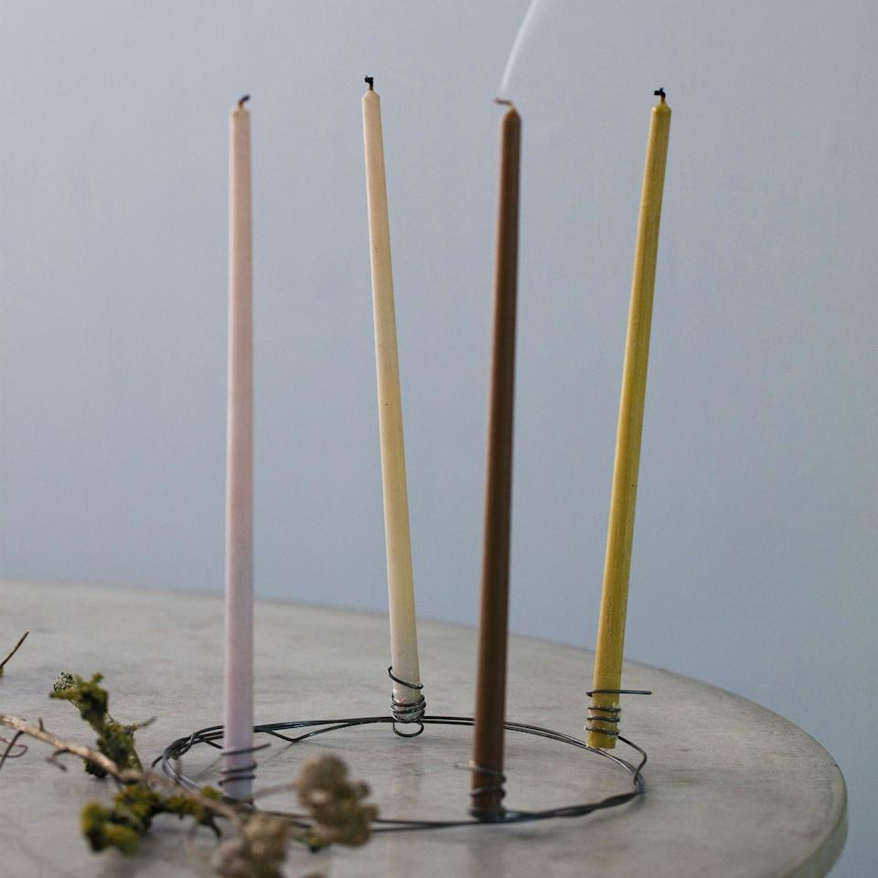 <p>Make an Advent wreath from thick steel wire. Create a circle from two layers of wire. Shape the ends of the wire around a thick pencil to create two of the candleholders. Take another piece of wire, twist it around the wreath and use the ends to make the two other candleholders.</p>