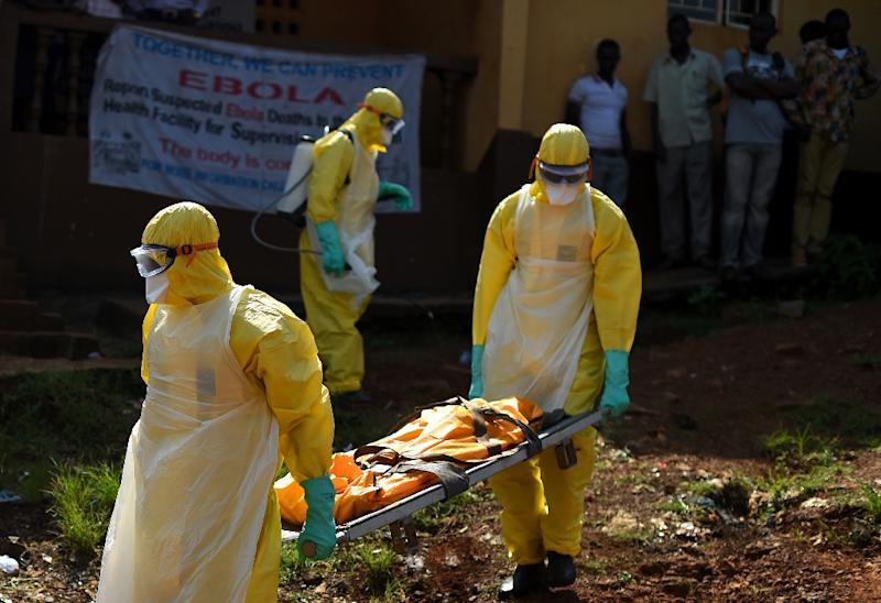 Health workers from Sierra Leone's Red Cross Society Burial Team 7 carry a corpse in Freetown on November 12, 2014 (AFP Photo/Francisco Leong)