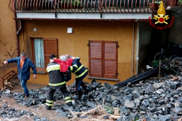 An elderly woman is rescued by firefighters following floods in Laglio, Lake Como, northern Italy, Tuesday, July 27, 2021. Towns around Italy's Lake Como hit by mudslides and floods on Tuesday, in yet an extreme example of extreme weather phenomenon that an agricultural lobby said Tuesday has intensified in recent years. Italian firefighters carried out more than 60 rescues after storms wreaked havoc around the picturesque lake ringed by mountains in northern Italy. They included bringing to safety an elderly woman blocked in her home, as well as a person with a disability and a caregiver isolated by a landslide. No deaths or injuries were reported. (Vigili del Fuoco via AP)