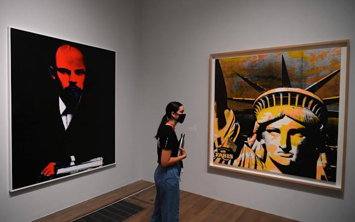 A visitor looks at Lenin, 1986 (L) and Statue of Liberty (Fabis) 1986 in the Andy Warhol exhibition at the Tate Modern in London on July 24, 2020, during a press preview - DANIEL LEAL-OLIVAS/AFP