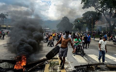 Anti-government activists build a barricade in Venezuela's third city, Valencia - Credit: AFP