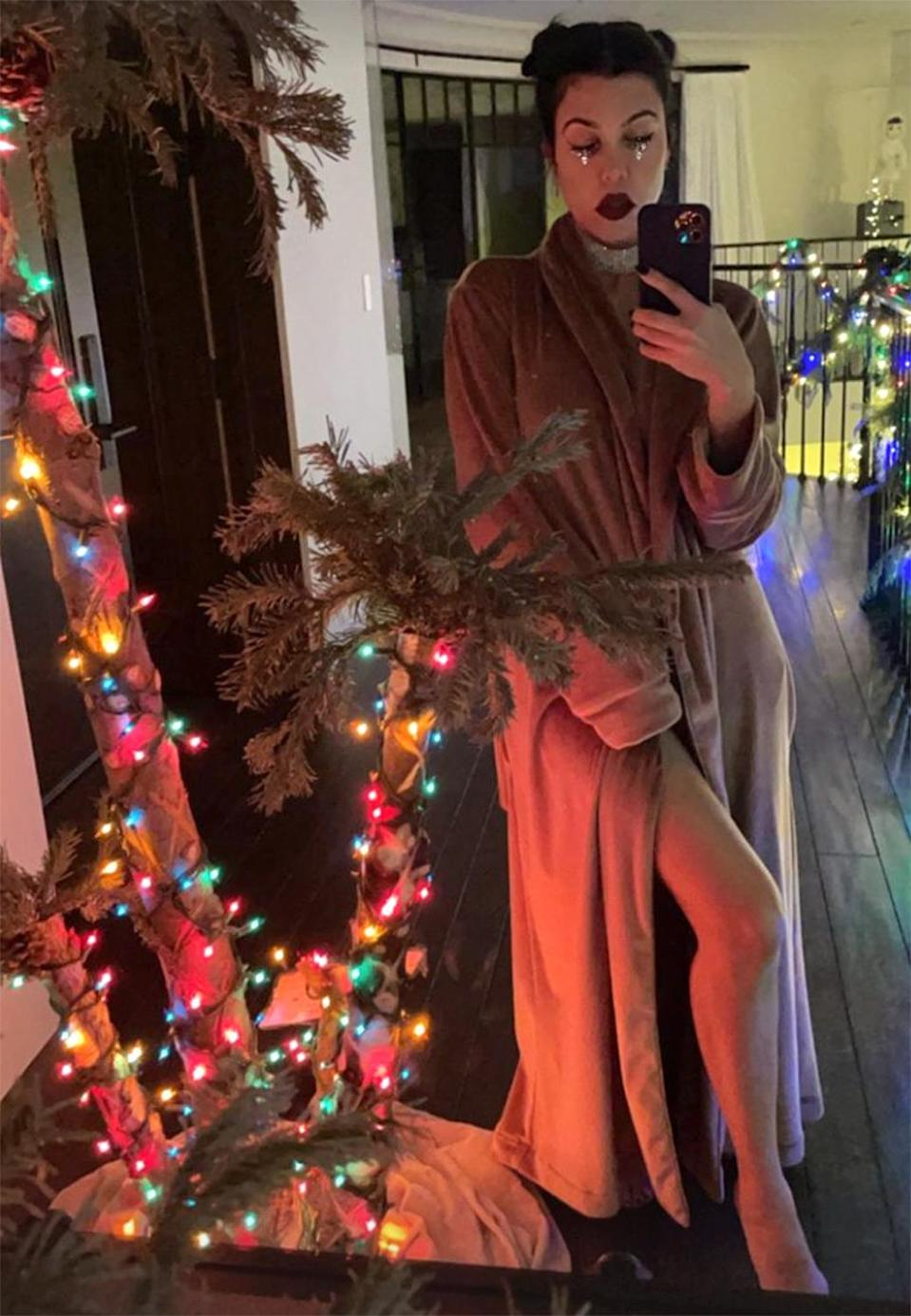 "<p>Kourtney looked <em>kozy</em> <a href=""https://www.instagram.com/kourtneykardash/"" rel=""nofollow noopener"" target=""_blank"" data-ylk=""slk:in a brown robe"" class=""link rapid-noclick-resp"">in a brown robe</a>, adding a dark lip and diamond choker for that New Year's Eve sparkle. </p>"