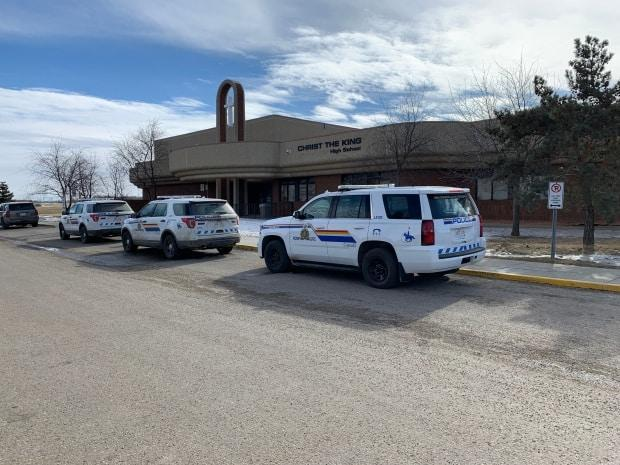 RCMP vehicles are seen parked outside Christ the King School in Leduc, Alta., Monday after what the school division said was a stabbing. According to RCMP, a student was airlifted to hospital in Edmonton, where she died of her injuries.  (Scott Neufeld/CBC - image credit)