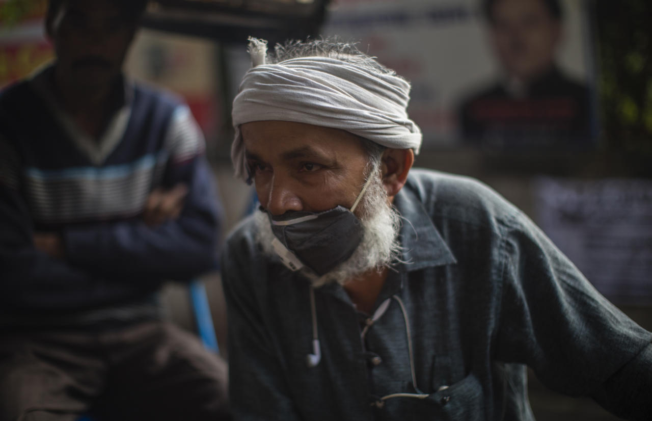 A rickshaw puller waits for passengers to ferry them on his rickshaw while wearing a protective mask amid coronavirus fear in New Delhi.