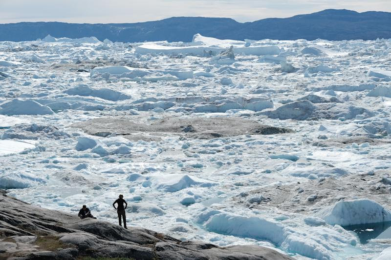 Visitors look out onto free-floating ice jammed into the Ilulissat Icefjord during unseasonably warm weather near Ilulissat, Greenland. (Photo: Sean Gallup/Getty Images)