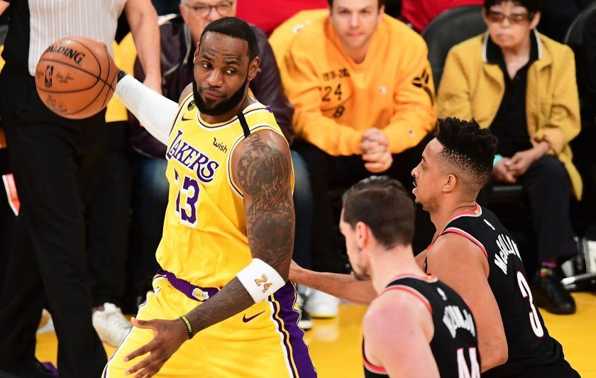 LeBron James of the Los Angeles Lakers looks to pass under pressure from CJ McCollum (R) and Mario Hezonja.