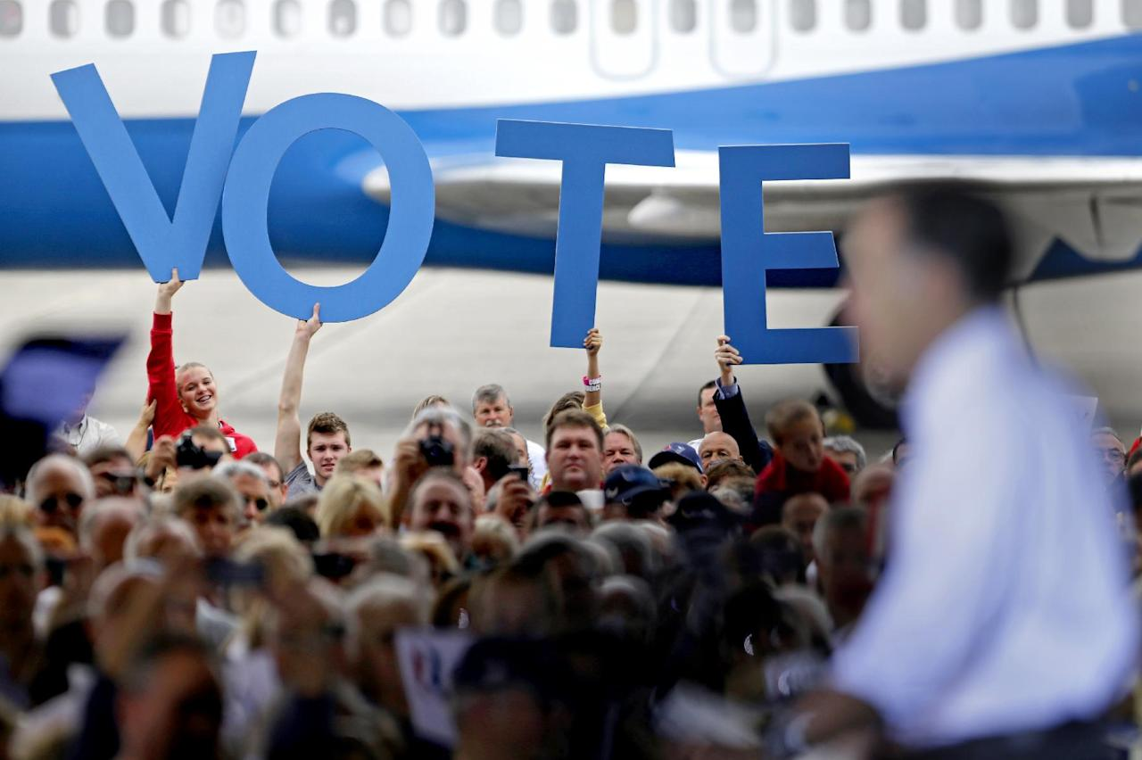 "Crowd members hold up a sign reading ""vote"" as Republican presidential candidate, former Massachusetts Gov. Mitt Romney speaks during a campaign event at the Orlando Sanford International Airport, Monday, Nov. 5, 2012, in Sanford, Fla. (AP Photo/David Goldman)"
