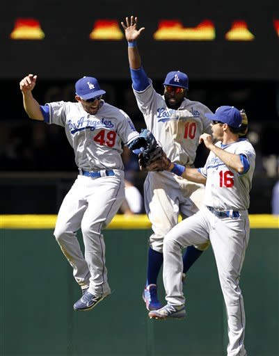 Los Angeles Dodgers outfielders Alex Castellanos (49), Tony Gwynn (10) and Andre Ethier (16) leap together as they leave the field after defeating the Seattle Mariners in a baseball game on Sunday, June 10, 2012, in Seattle. The Dodgers won 8-2. (AP Photo/Elaine Thompson)