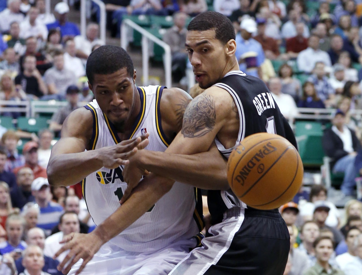 Utah Jazz forward Derrick Favors, left, passes around San Antonio Spurs guard Daniel Green during the first half of an NBA basketball game Monday, April 9, 2012, in Salt Lake City. (AP Photo/Jim Urquhart)