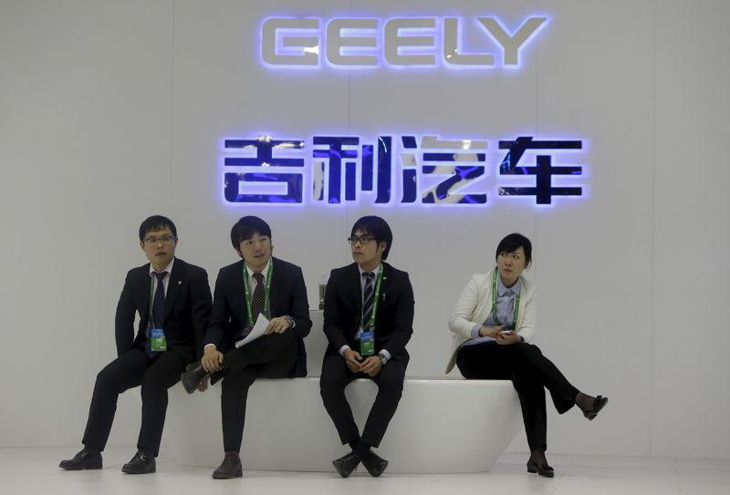 File picture of staff members sitting in front of a Geely signage at Auto China 2014 in Beijing