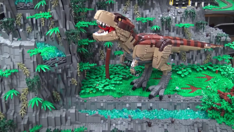A LEGO build featuring a giant T-rex and working, motorized LEGO waterfall.