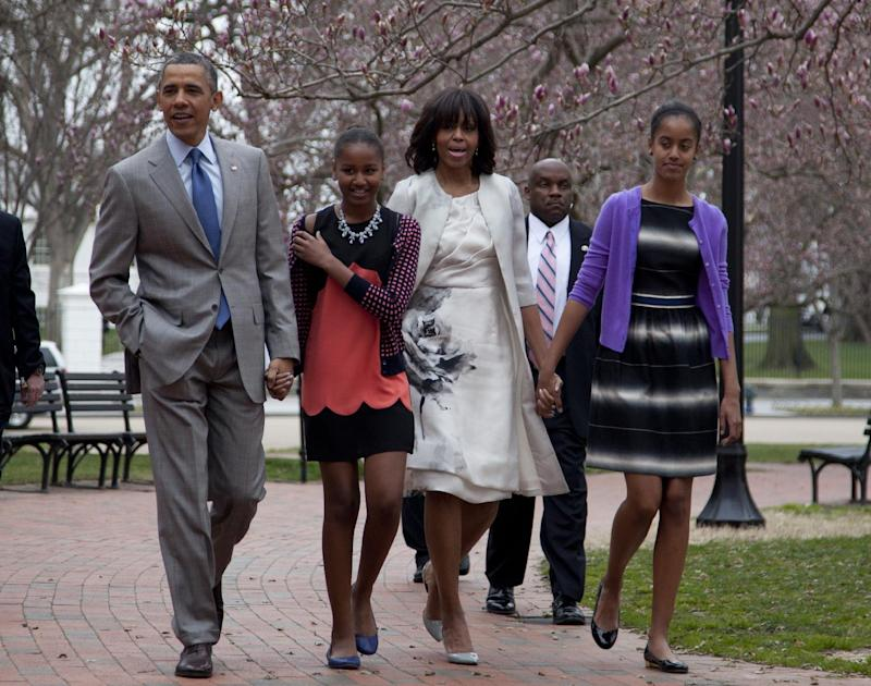 President Barack Obama and first lady Michelle Obama walk from the White House with their daughters Sasha Obama, second from left, and Malia Obama, right, on their way through Lafayette Park to St. John's Episcopal Church for Easter services, Sunday, March 31, 2013, in Washington. (AP Photo/Carolyn Kaster)
