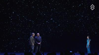 Blockchains, LLC Founder and CEO Jeffrey Berns, left, and company president David Berns reveal the long-awaited details of a blockchain-based smart city to a crowd of developers next to a hologram to their global launch during Blockchain Week Prague. Visual effects for the holograms of the event were created by Digital Domain.