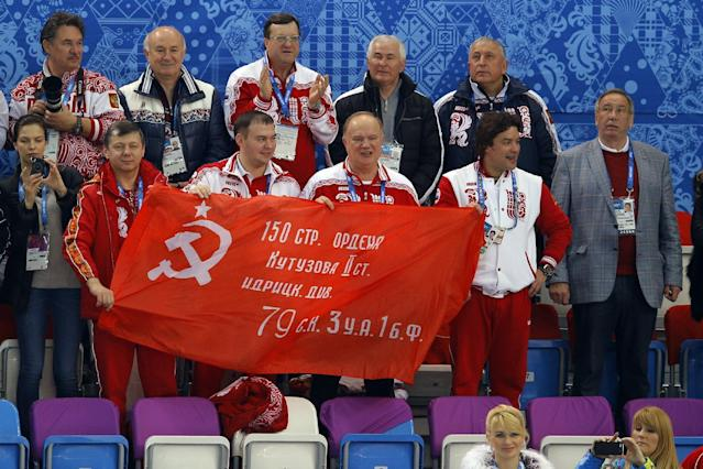 Russian Communist Party leader Gennady Zyuganov, bottom row center, holds the Soviet Banner of Victory with others during a flower ceremony for the short track speedskating competition at the Iceberg Skating Palace during the 2014 Winter Olympics, Friday, Feb. 21, 2014, in Sochi, Russia. The banner is a replica of the flag raised by Soviet soldiers in Berlin in 1945, in victory over Nazi Germany. (AP Photo/Vadim Ghirda)