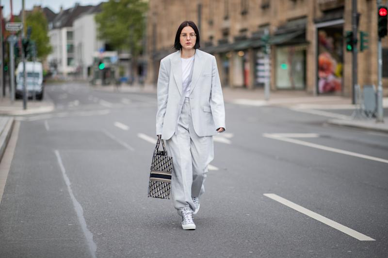 DUESSELDORF, GERMANY - MAY 05: Maria Barteczko is seen wearing grey linen oversized blazer Stella McCartney, white tshirt The Row, grey inen wide leg trousers Stella McCartney, logo book tote bag Dior, logo high top chucks Dior, round retro glasses Ray Ban, rings APM Monaco on May 05, 2019 in Duesseldorf, Germany. (Photo by Christian Vierig/Getty Images)
