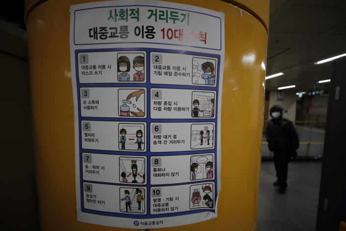 "A man wearing a face mask walks near a banner displaying precautions against the coronavirus at a subway station in Seoul, South Korea, Sunday, Dec. 27, 2020. The banner reads: ""Social distancing for public transportation."" (AP Photo/Lee Jin-man)"