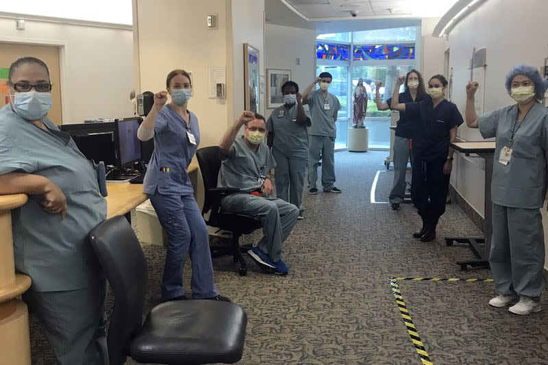 Nurses at Providence Saint John's Health Center in Santa Monica, Calif., on April 9, raise their fists in solidarity after telling managers they can't care for COVID-19 patients without N95 respirator masks to protect themselves.(Lizabeth Baker Wade/AP)