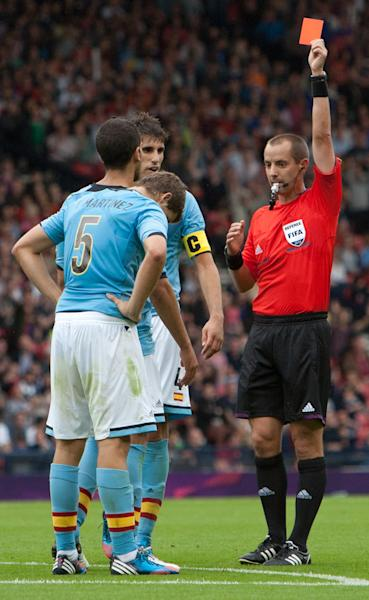FILE - In this Thursday July 26, 2012 file photo Spain's Inigo Martinez, left, is shown a red card by referee Mark Geiger during the group D men's soccer match between Japan and Spain at the London 2012 Summer Olympics at Hampden Park Stadium in Glasgow, Scotland. Mark Geiger aims to become the first American referee to advance from the group stage in the World Cup in Brazil. (AP Photo/Chris Clark, File)