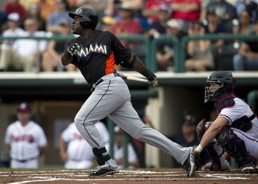 Atlanta Braves catcher Jose Yepez, right, watches as Miami Marlins' Marcell Ozuna hits a three-run home run during the first inning of an exhibition spring training baseball game on Sunday, March 10, 2013, in Kissimmee, Fla. (AP Photo/Evan Vucci)