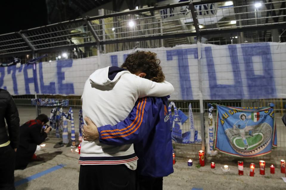 Two supporters hug each other outside the San Paolo Stadium as people gathered and pay their homage to soccer legend Diego Maradona, in Naples, Italy, Wednesday, Nov. 25, 2020. Diego Maradona has died. The Argentine soccer great was among the best players ever and who led his country to the 1986 World Cup title before later struggling with cocaine use and obesity. He was 60. (AP Photo/Alessandra Tarantino)