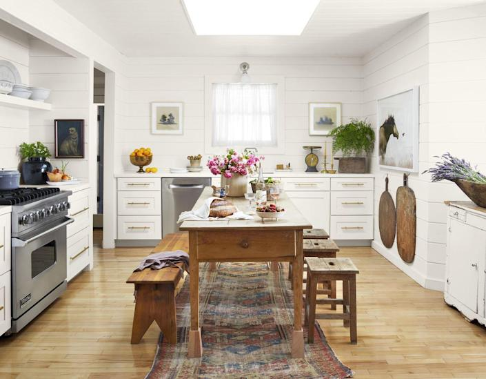 <p>To add air to the 11-by-13-foot kitchen, these homeowners chose to omit upper cabinets and install a skylight for maximum natural light. An antique French farm table that acts as both a work island and an eat-in setup and framed artwork situated throughout the space make it feel more like a room than a kitchen. The walls are painted Simply White by Benjamin Moore. </p>