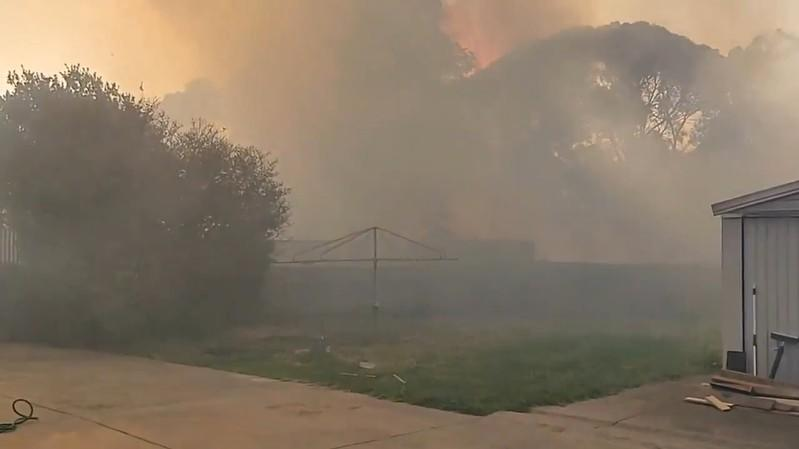 Social media video grab shows smoke from bushfires engulfing an area in Paradise City