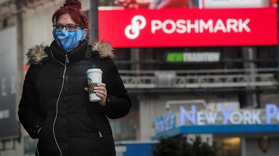 """A woman walks through Times Square as a screen displays the company logo for Poshmark Inc. during it""""s IPO at the Nasdaq Market Site in Times Square in New York City, U.S., January 14, 2021."""