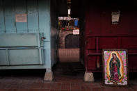 A framed painting depicting Our Lady of Guadalupe is propped against a shuttered market stall on empty Olvera Street in downtown Los Angeles, Wednesday, Dec. 16, 2020. Olvera Street, known as the birthplace of Los Angeles, has been particularly hard hit by the coronavirus pandemic, with shops and restaurants closed and others barely hanging on. (AP Photo/Jae C. Hong)