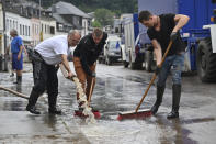 People are cleaning up the damage in Kordel, Germany, Friday, July 16, 2021 after the flooding of the Kyll river two days ago. Heavy rains caused mudslides and flooding in the western part of Germany. Multiple have died and dozens are missing as severe flooding in Germany and Belgium turned streams and streets into raging, debris-filled torrents that swept away cars and toppled houses. (Harald Tittel/dpa via AP)