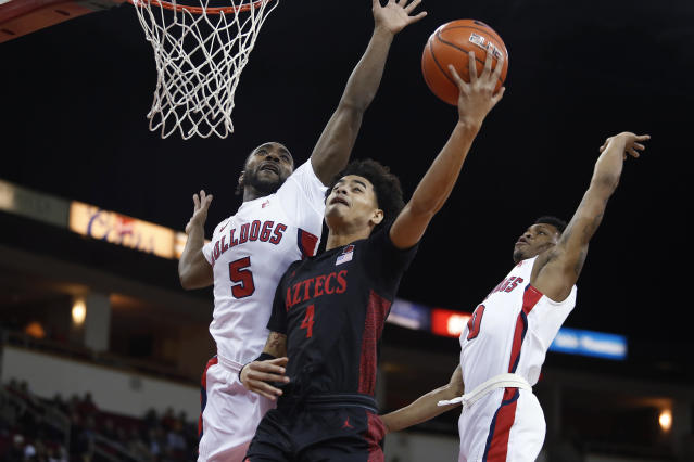 San Diego State's Trey Pulliam goes in for a layup against Fresno State's Jordan Campbell, left, and New Williams, right, during the first half of an NCAA college basketball game in Fresno, Calif., Tuesday Jan. 14, 2020. (AP Photo/Gary Trey Pulliam