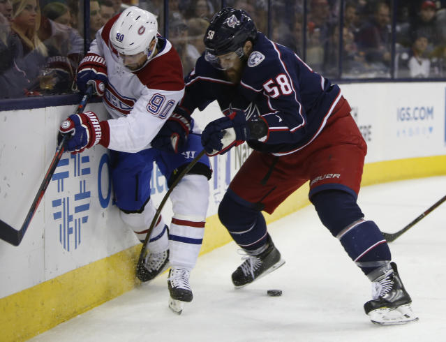 Montreal Canadiens' Tomas Tatar, left, of Slovakia, and Columbus Blue Jackets' David Savard fight for the puck during the first period of an NHL hockey game Thursday, March 28, 2019, in Columbus, Ohio. (AP Photo/Jay LaPrete)