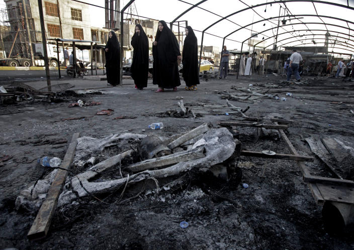 FILE - In this Sunday, Sept. 22, 2013 file photo, people inspect the site of a double suicide bomb attack in the Shiite neighborhood of Sadr city in Baghdad, Iraq. (AP Photo/Karim Kadim, File)
