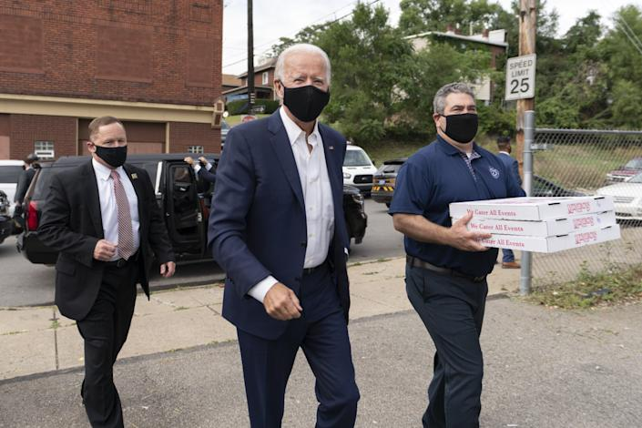 Democratic presidential candidate Joe Biden arrives with pizza as he visits firefighters in Pittsburgh in August.