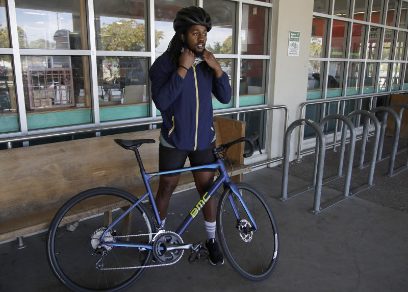 In this Friday, May 15, 2020 photo, Joel Johnson adjusts his helmet as he prepares to ride his new bicycle at the Sports Basement store in San Francisco. Johnson hadn't owned a bicycle since he was 15, but soon after the coronavirus pandemic led to a shelter in place order in San Francisco, he bought a bike to avoid crowded public trains and buses. JHe is among thousands of cooped-up Americans snapping up new bicycles or dusting off decades-old bikes to stay fit, keep their mental sanity or have a safe alternative to public transportation. (AP Photo/Ben Margot)