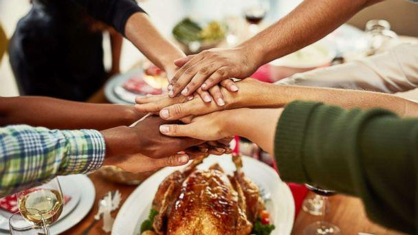 PHOTO: A family stacks their hands in celebration before a special dinner. (PeopleImages/Getty Images)