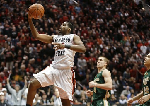 San Diego State guard Chase Tapley leaves the Colorado State defenders in his wake as he scores after a steal during overtime in San Diego State's 79-72 victory in an NCAA college basketball game Saturday Jan. 12, 2013, in San Diego. Tapley scored 12 points in overtime. (AP Photo/Lenny Ignelzi)